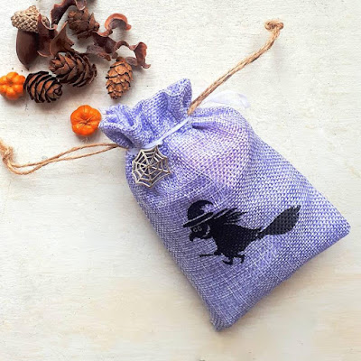 A small purple hessian bag with a witch printed on it next to some halloween potpourri