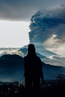 girl in front of smoking volcano