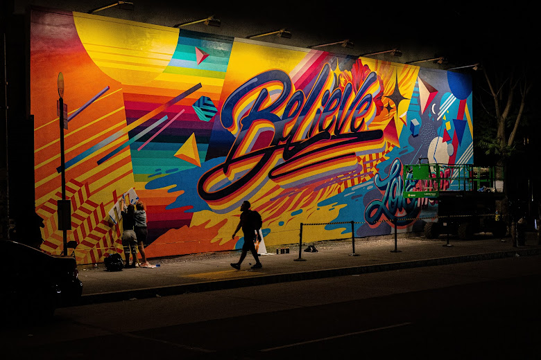 A brightly colored wall painted on a street which says,'believe'