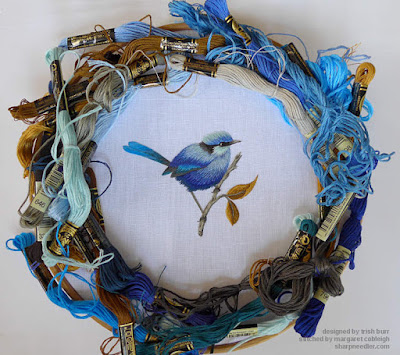 Thread painted blue bird surrounded by threads used to stitch the design