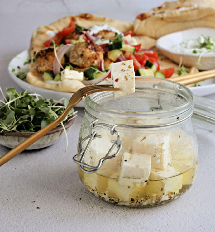 Recipe for crispy baked chicken meatballs with oregano, tzatziki sauce and marinated feta cheese.