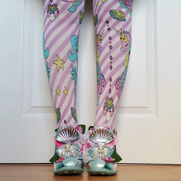 front facing feet wearing shoes with open oyster and large pearl detail on t-bar