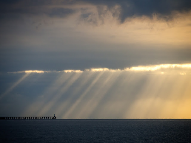 Photo of the sun breaking through heavy clouds over Maryport pier