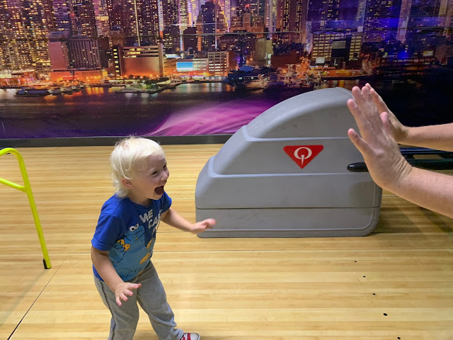 Excited 3 year old in a bowling alley