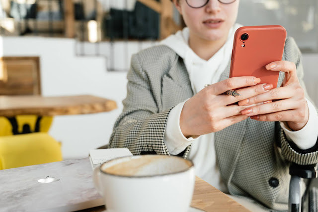 A person having coffee while browsing something on their phone.