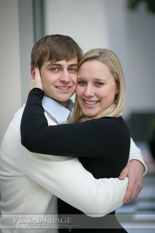 Engaged couple holding each other and looking at camera while smiling