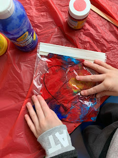 child's hands pressing on paint inside heart drawn on ziploc bag