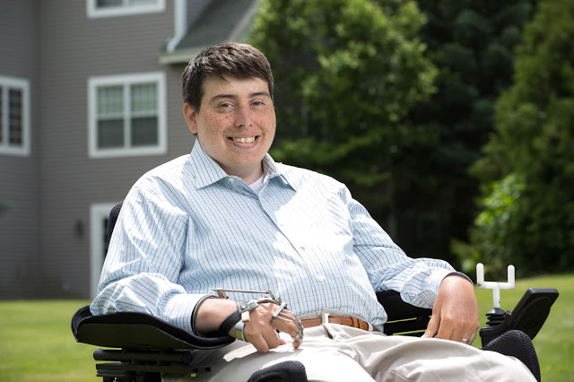 Photo of Jimmy Anderson, a young, half Hispanic, half white man with short brown hair. He is sitting in a power chair with a long-sleeved blue and white striped shirt and khaki pants. Behind him is a green lawn, a home and tree. He is smiling at the camera.