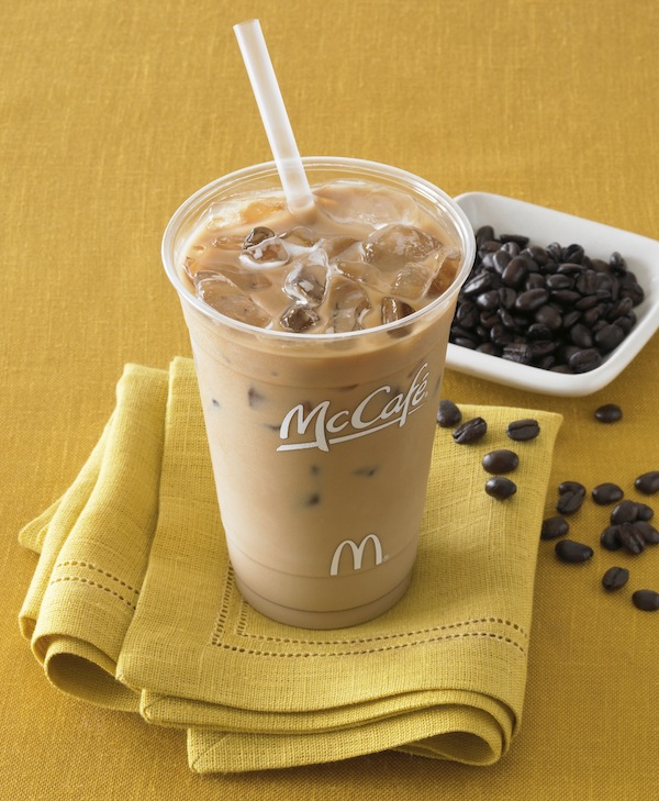 iced coffee in McDonald's cup with straw on folded gold napkin with coffee beans in small white dish and more strewn artfully about the table