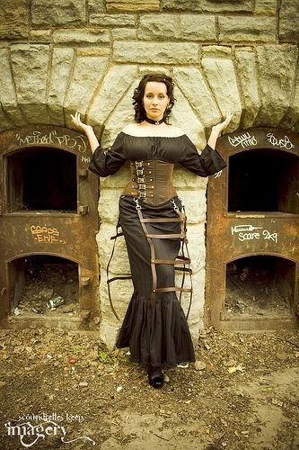 Woman wearing Steampunk clothing consistsing of a black peasant blouse and black peasant skirt, brown leather corset with attached cage skirt petticoat