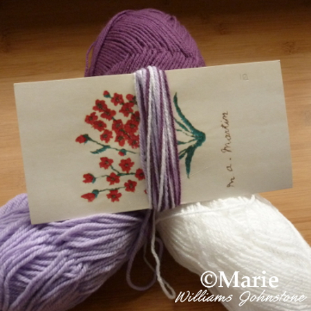 white and lilac colored wools yarns wrapped on card
