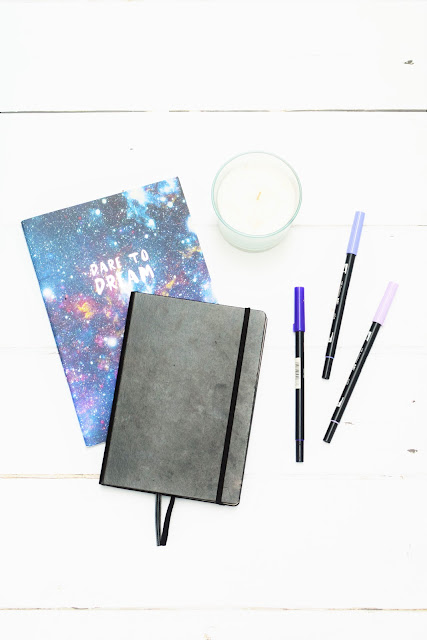 A picture of a black bullet journal, notebook with galaxy print with the message Dare To Dream, three brush pens and a candle