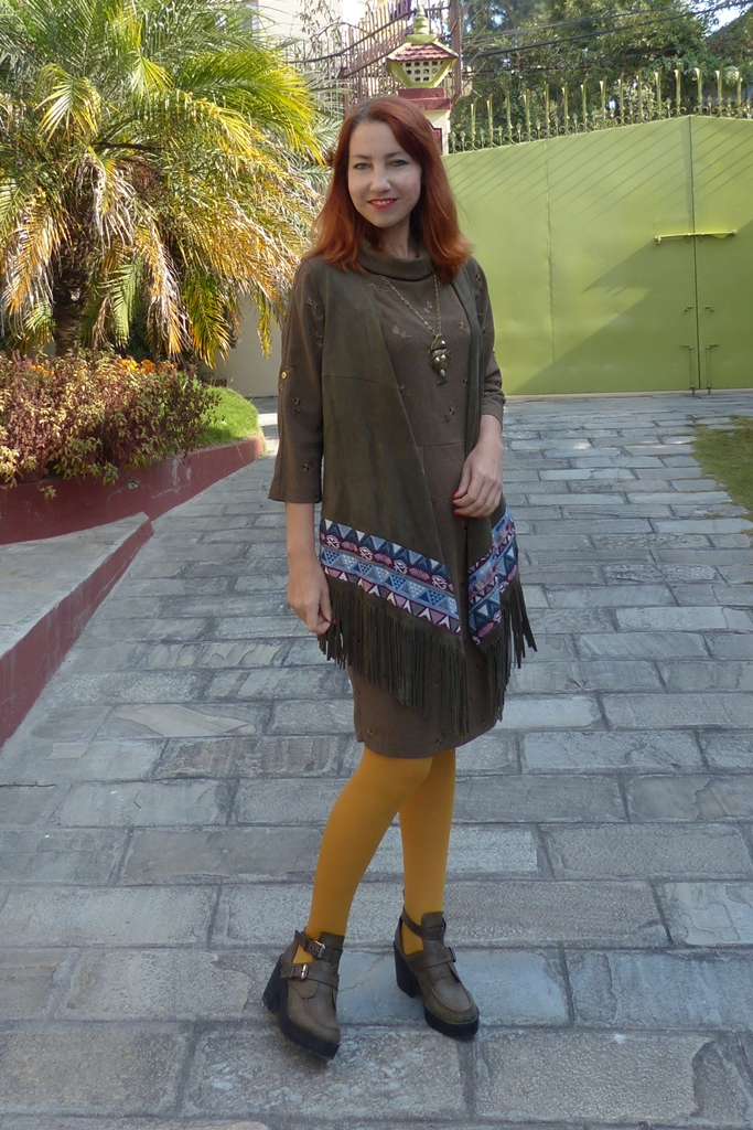 Dark olive fringed vest worn over a dress
