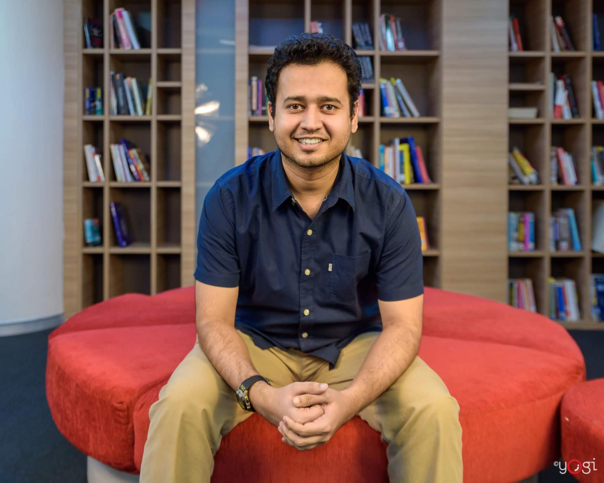Image shows Bhavesh Bhatt seated and smiling at the camera