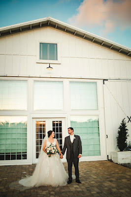 bride and groom in front of barn at Ever After Farms