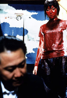 Standing girl covered in blood looking at seated man who ignores her