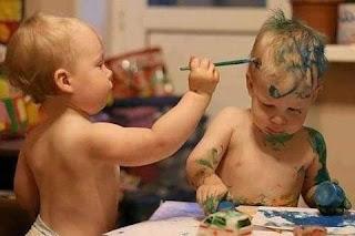 Niño pinta con pincel y pintura a hermano