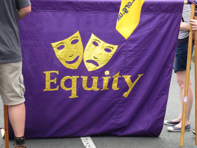 Equity banner. Purple with gold faces of drama. Comedy and Tragedy.