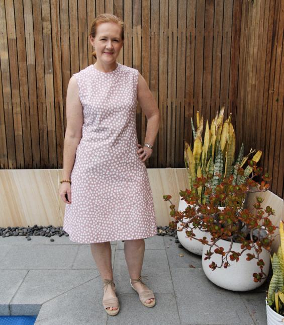 a woman posing in a pink polka dot dress