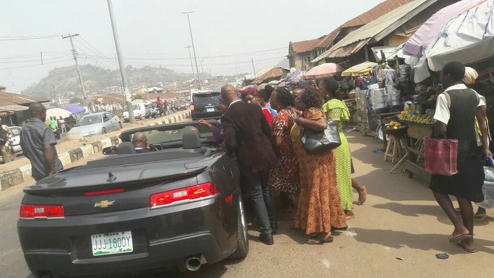 Fayose cruises in convertible Chevrolet sports car as he greets market women
