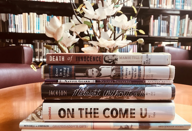 books are stacked on a small table in front of library shelves. fake magnolia behind stacked books. the books are death of innocence, ever is a long time, native guard, midnight without a moon, on the come up, and granddaddy's gift