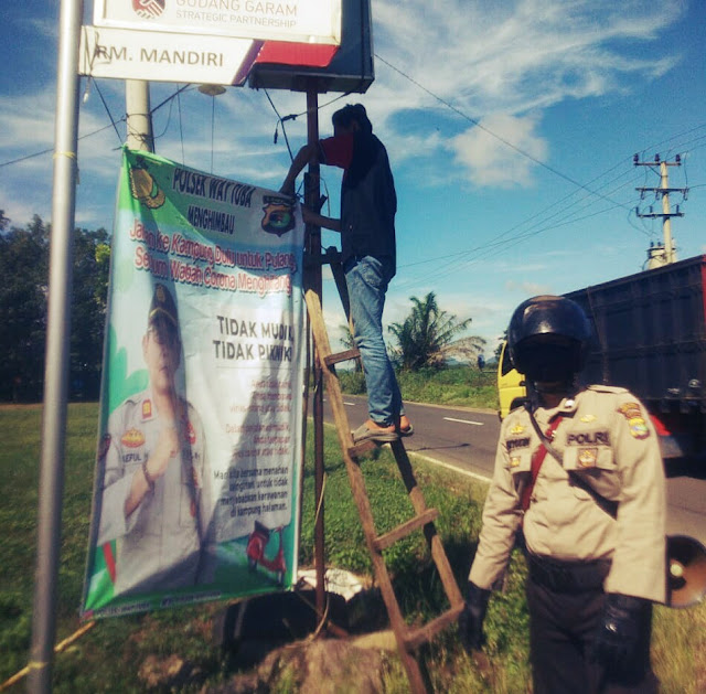 Personil Polsek Way Tuba memasang spanduk himbauan dari Kapolsek Way Tuba untuk stop perjalanan mudik