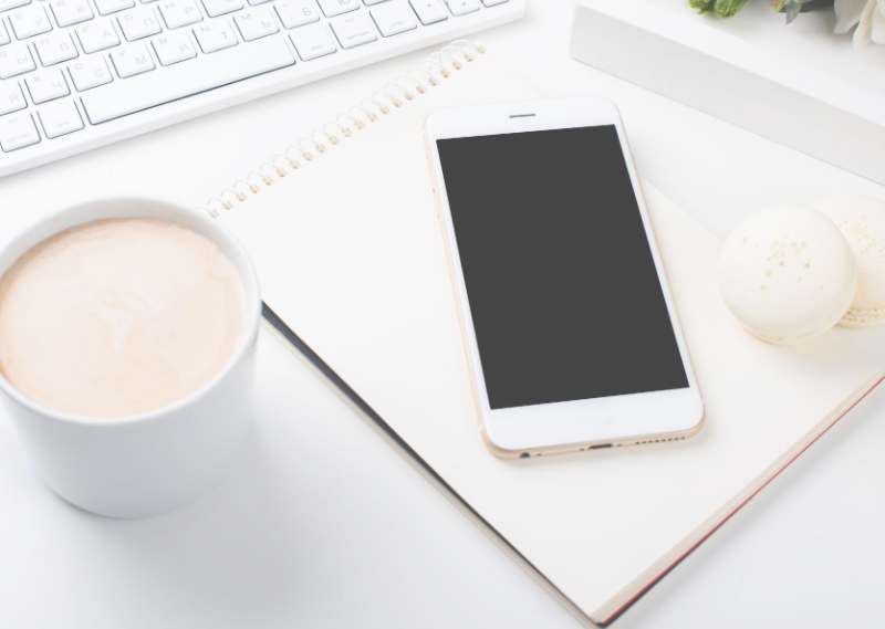 A desk with a phone and coffee in a post about setting my monthly goals for August 2020.