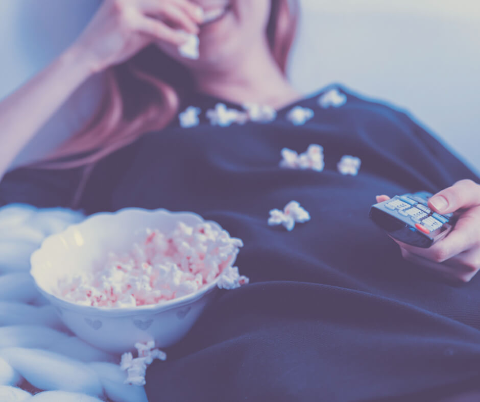 A woman sits eating popcorn while holding a television remote control.