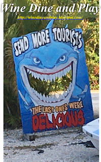 A tourist sign of a shark saying to send more so that they can be eaten outside the Hooked Island Grill in Matlacha, Florida