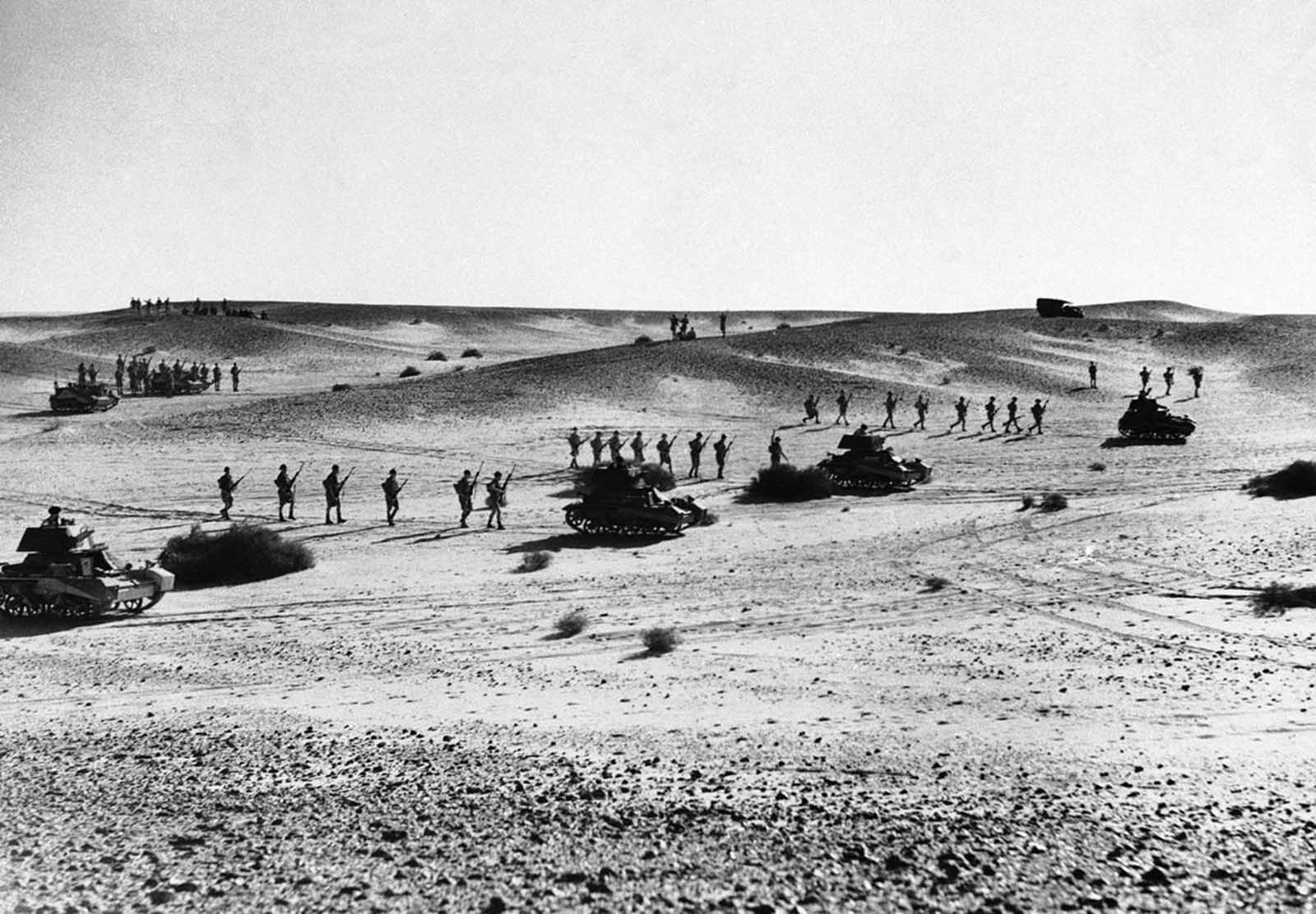 Australian troops string out behind tanks in a practice advance over North African sands, on January 3, 1941. The supporting infantry is spread out thinly as a precaution against air raids.
