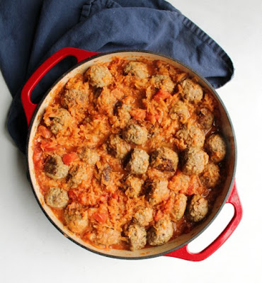 enameled cast iron pan filled with meatballs and homemade sauce