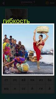 на берегу женщина с корзиной на голове демонстрирует свою гибкость перед зрителями