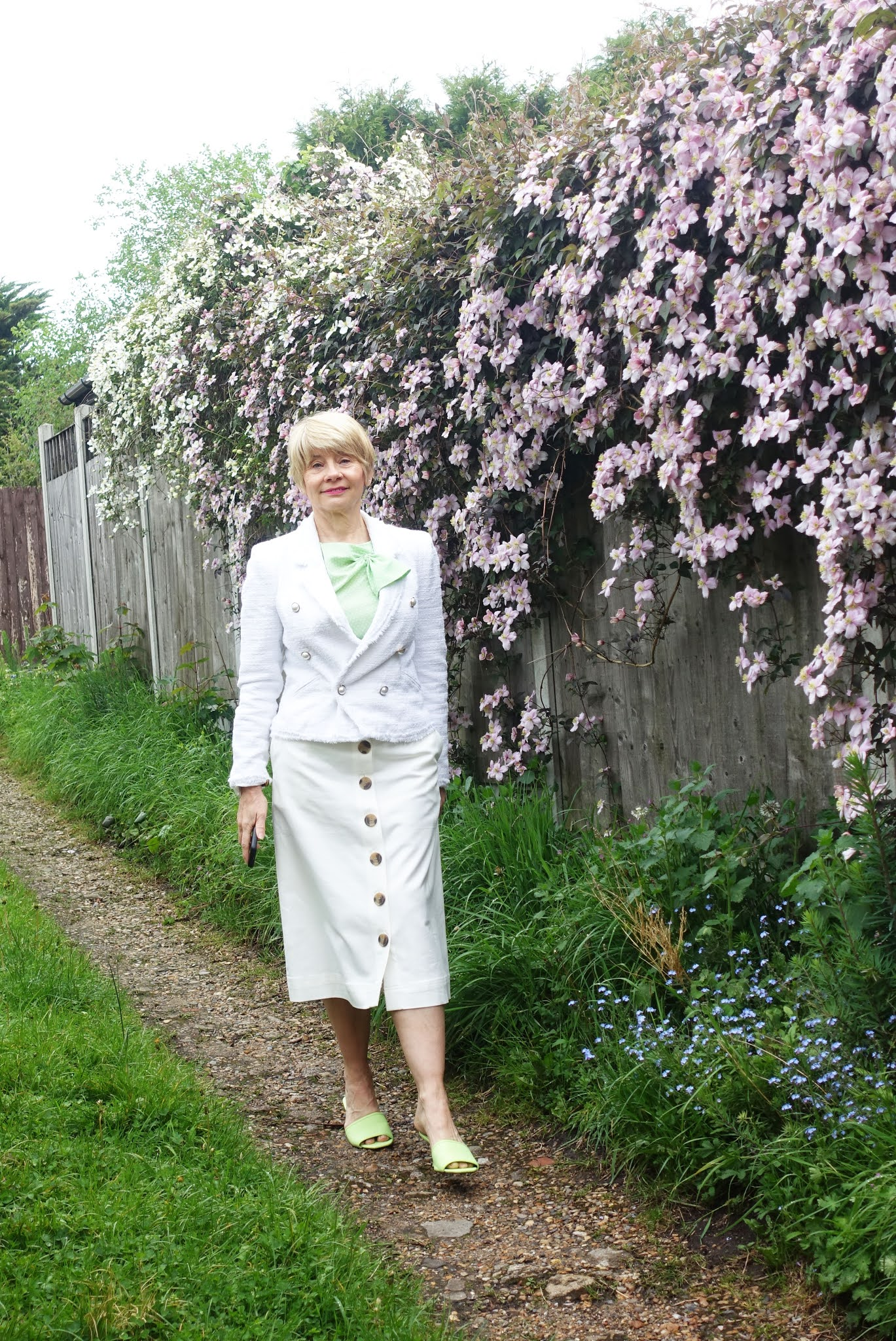 Taking a stroll past her clematis montana in full bloom:  Gail Hanlon from over-50s style blog Is This Mutton