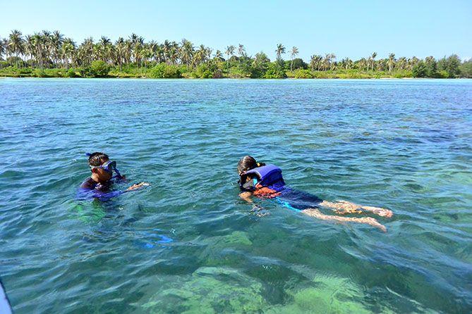 Pemandu memotret wisatawan saat snorkeling