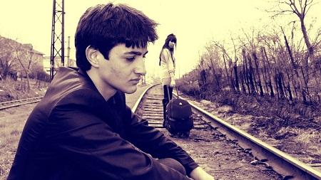 Sad Young Couple Sitting On Railway Track
