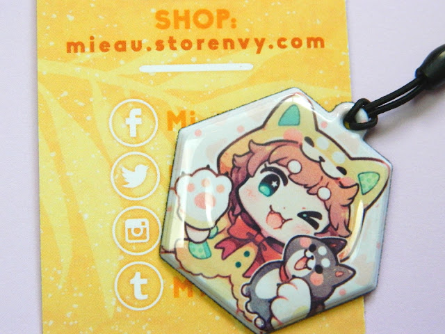 A charm made by an online store called Mi-eau, showing a shiba inu girl
