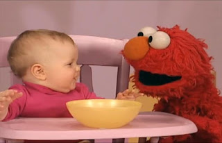 Later Elmo and a baby are on the stage. The baby puts his hand in the bowl. Sesame Street Elmo's World Hands Kids and Baby