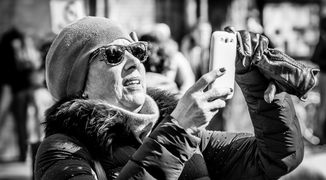 black and white photo. Grandma takes a glove off to use her cell phone. Speak Your Mind and other stories of Grandmas and reason. marchmatron.com