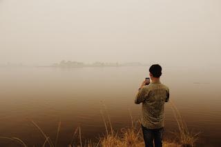 memotret landscape di tepi danau yang kabut