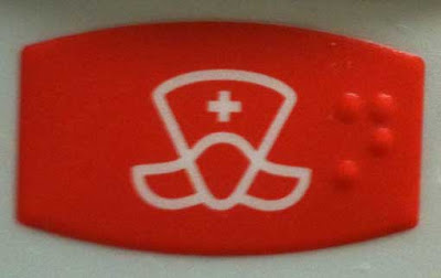 red button with white outline art in an odd shape with a small white cross in the center