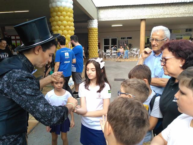 Artista de Humor e Circo interagindo com truques de mágica com o público de evento do dia das crianças.