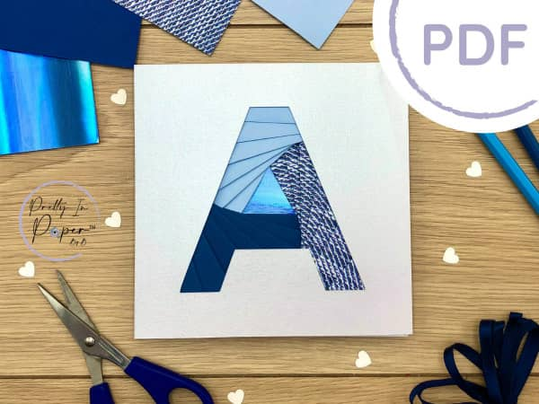 iris folded block letter A greeting card shown with paper crafting supplies