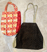 Two tote bags. A larger one in brown with pale green print and a smaller one with red and yellow prints