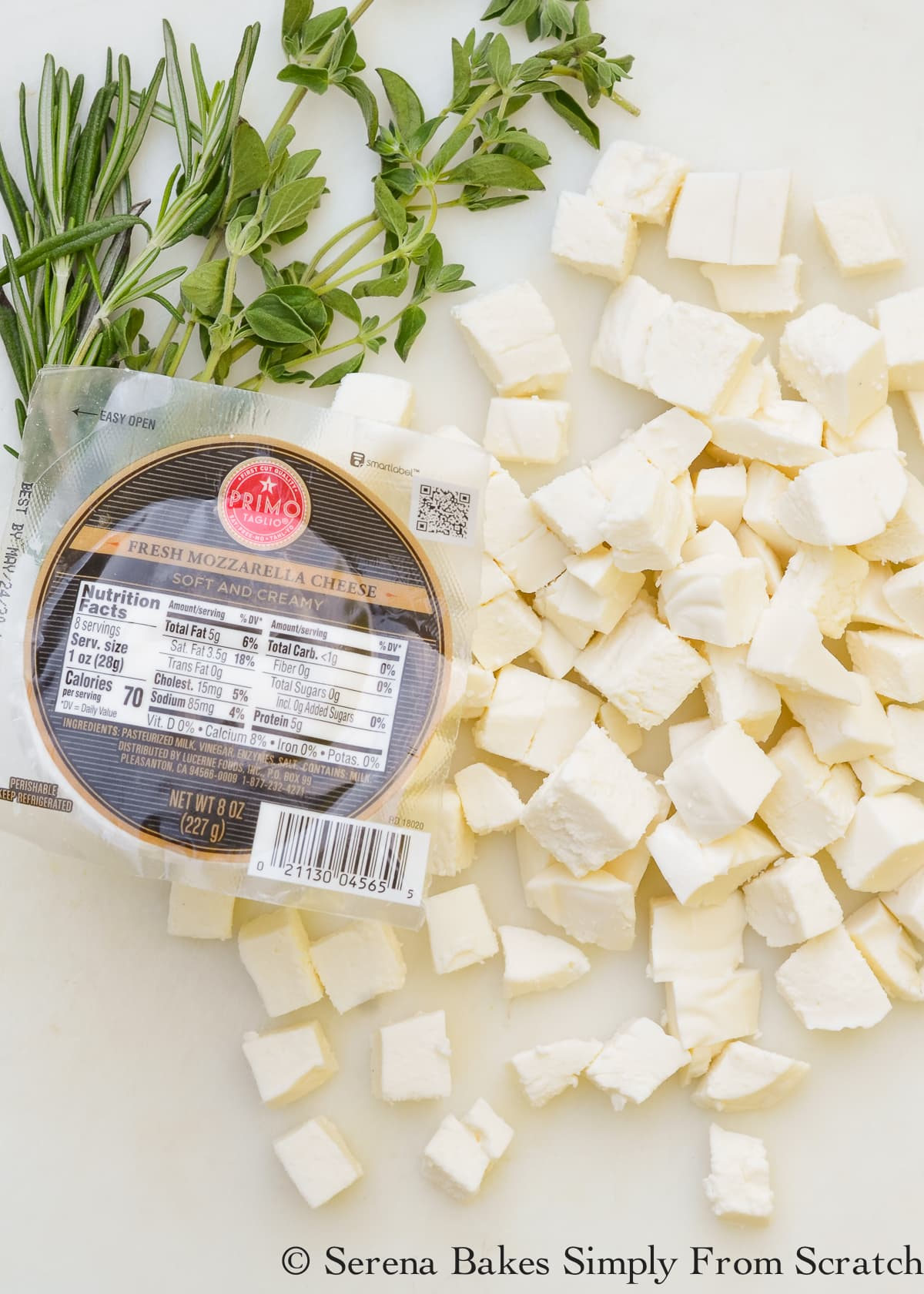 A package of fresh mozzarella cheese and cubed fresh mozzarella cheese on a white cutting board.