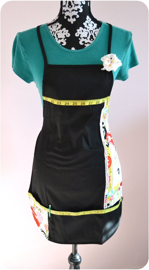 Black and decorative fabric sewing apron with pin cushion, measuring tape and pockets for sewing supplies.