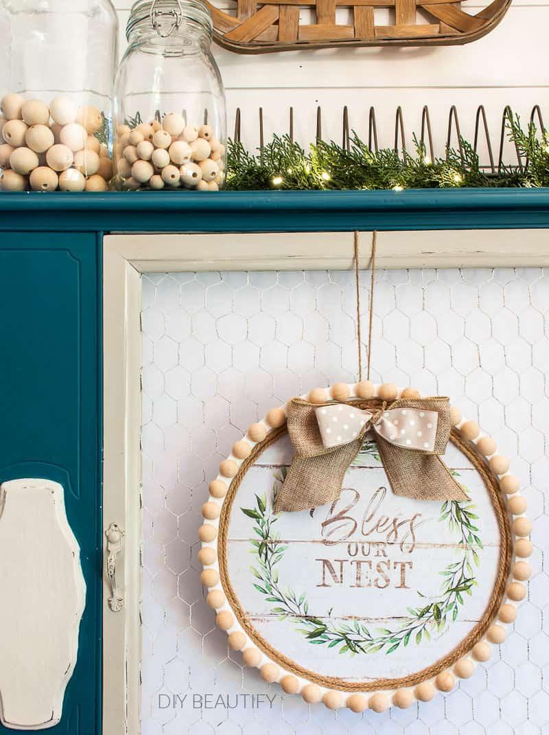 bless our nest farmhouse wreath on blue cabinet