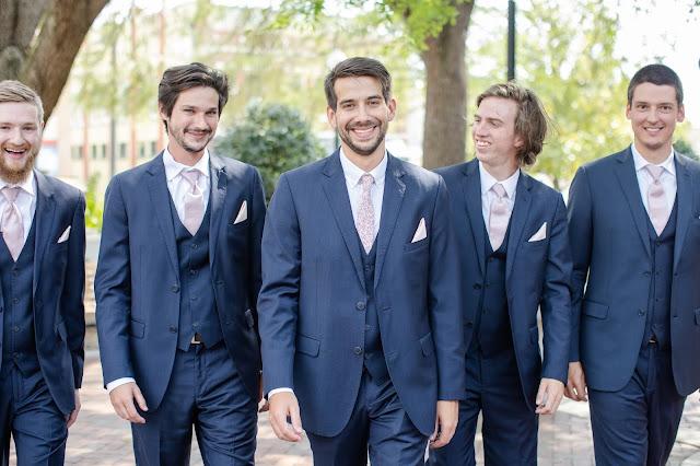 groom and groomsmen in navy suit with pink ties