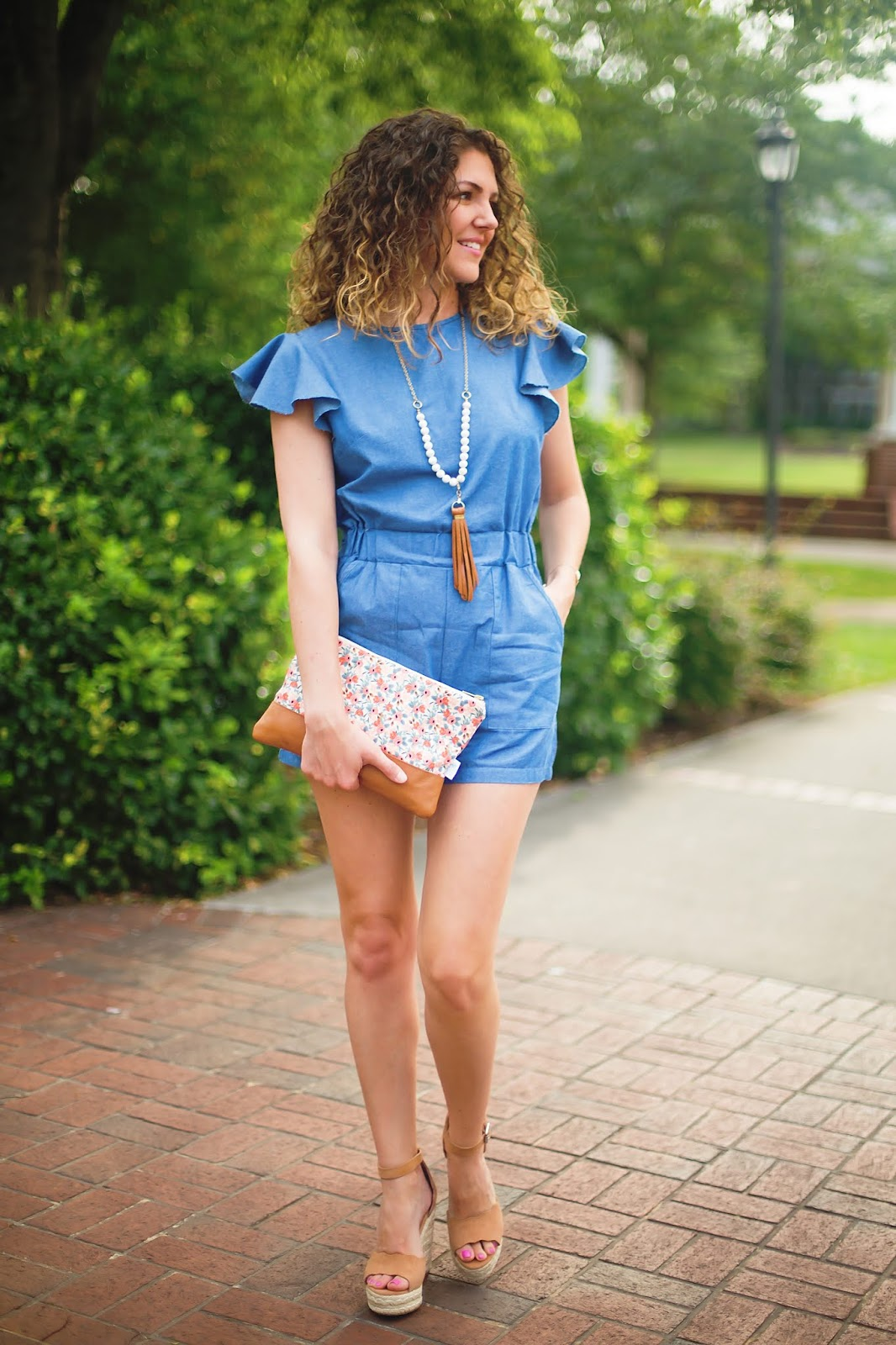 Jenn Pennell, Shaw Avenue blog, wears a denim romper from Amazon, Steve Madden scalloped wedges, floral clutch, and leather necklace.