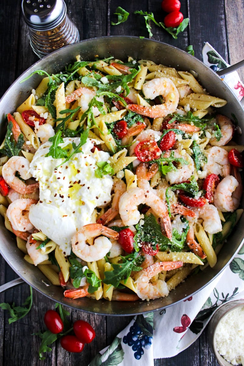Top view of Shrimp, Arugula, and Burrata Pasta in a stainless steel skillet on a wood background.