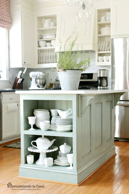 white kitchen with blue kitchen island with white chine on the shelf